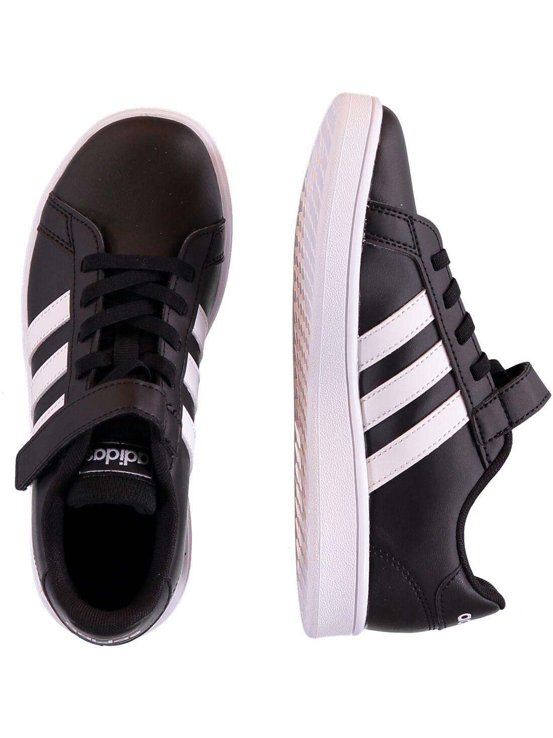 Basket Adidas en cuir synthétique noir avec trois bandes blanches sur le côté. Doublure et semelle intérieure en textile. Fermeture pratique à bande